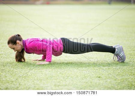 Sporty beautiful young woman practicing yoga, doing chaturanga dandasana, push-ups, four-limbed staff posture, working out outdoors on summer day wearing sportswear sweatshirt. Full length, side view