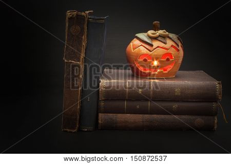 Pumpkin lantern for Halloween and the old witch books. Head carved from a pumpkin on Halloween. Pumpkin tradition. The book of spells, magical book. Textbooks for witches.
