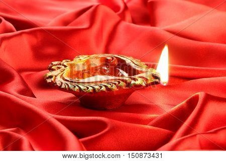 Handmade Diwali Clay Lamp on Red Satin Background