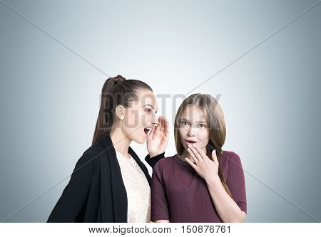 Two college students in casual clothes are gossiping against gray blackboard. Concept of rumor circulation. Mock up