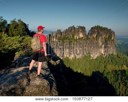 Sunny Day In Mountains. Hiker With Red Cap, Backpack And Poles On Rock