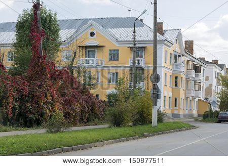 The three-storey building orange yellow built in 30-ies of the 20th century next to an asphalt road and Bush vines along the streets with trees autumn Russia the city of Novomoskovsk street birch