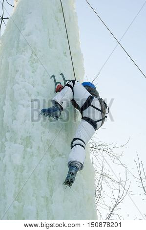 Tyumen, Russia - January 19, 2008: Tower which is filled in with water near Children Club of Kizhevatov name. Ice climbing competition. Girl climbs upward