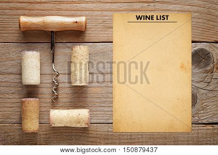 Corkscrew with corks and wine list template on wooden background