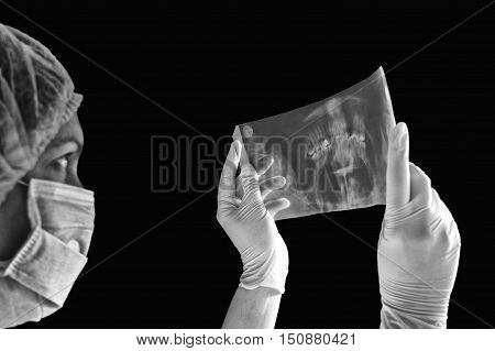 Female doctor examining an x-ray isolated on black background. Selective focus on x-ray image.