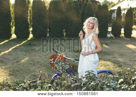 Girl with wild flowers and bicycle walks in the garden.