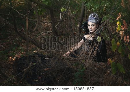 Gothic girl in black clothes is sleeping in the woods.