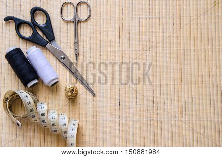 Sewing accessories on beige background with copyspace. Scissorscentimetre bobbins with thread and needles .
