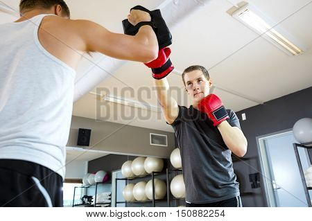 Low angle view of young male boxer punching bag held by instructor in gym
