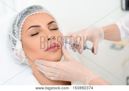 Young woman is getting botox injection into her face at clinic. Her eyes are closed with relaxation