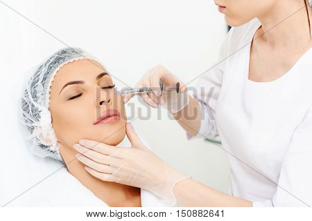 Professional doctor is making botox injection into female eye area. She is sitting and holding syringe