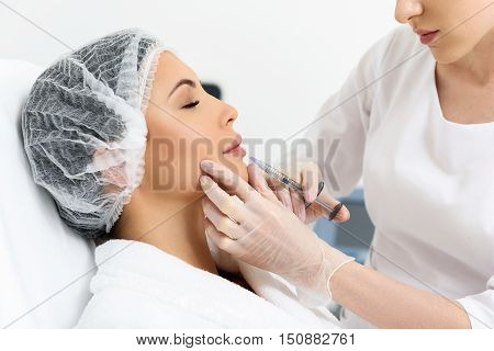 Sensual young woman is getting facial botox injection at clinic. Her eyes are closed with serenity. Female doctor is sitting and holding syringe near her lips