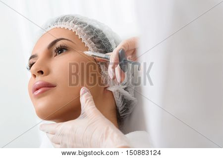 Close up of beautician hands holding syringe with botox liquid near female face. Young woman is looking forward with serenity