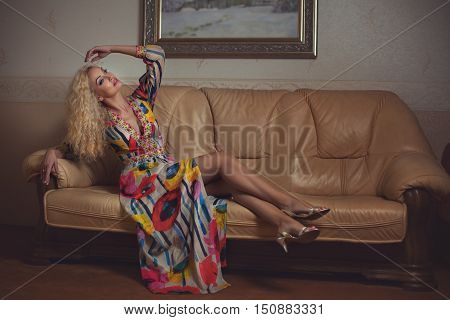 Blonde lying on a couch in a bright dress.