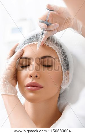 Experienced doctor rejuvenates female facial skin. She is standing and injecting botox into woman forehead accurately