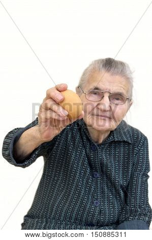 Old woman holding an organic egg. Selective focus on egg.