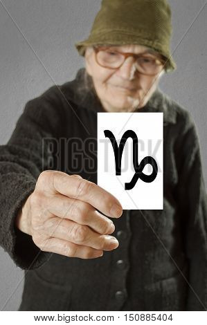 Elderly woman holding card with printed horoscope Capricorn sign. Selective focus on card and fingers.