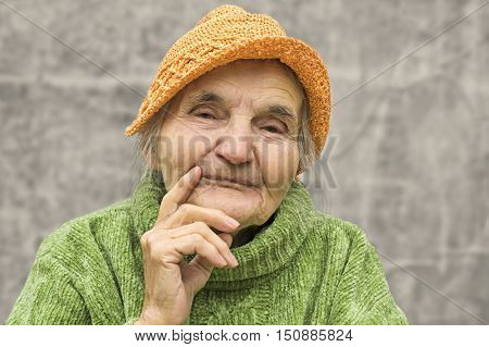 Portrait of a thoughtful elderly woman. Dreaming the past.