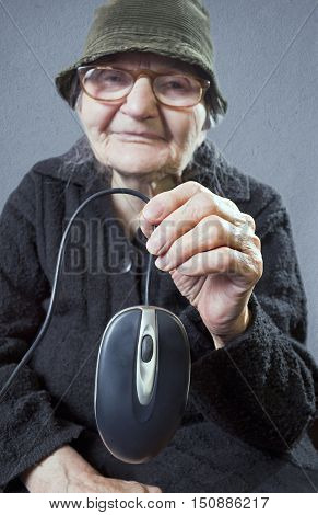 Elderly woman holding up a computer mouse. Selective focus om computer mouse.