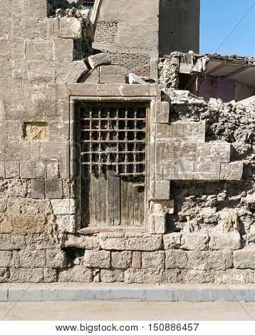Old abandoned wall with one closed wooden window covered by broken wooden iron grid El-Dard El-Ahmar Cairo Egypt
