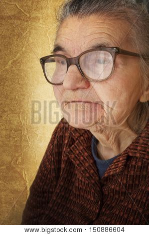 Portrait of an old woman on a vintage background. Dreaming the past