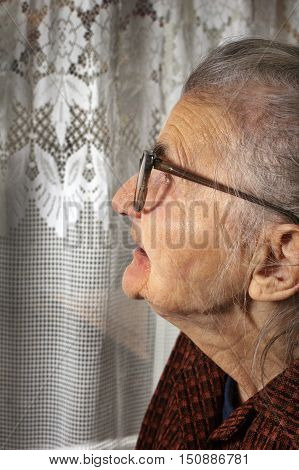 Old woman at the window dreaming the past