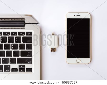 CHIANGRAI THAILAND -SEPTEMBER 7 2016: Top view (Flat lay) image of two way external flash storage between the Apple Macbook Pro Retina and Apple iPhone 6 on white background Minimalist
