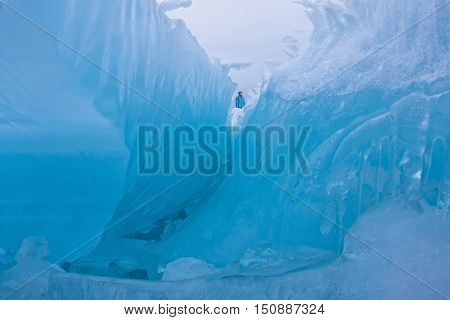 Girl Standing On The Wave Of Blue Ice Blocks At Dusk. Lake Baikal