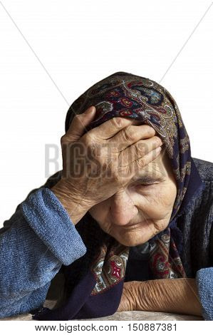 Portrait of a sad elderly woman holding her head in pain.