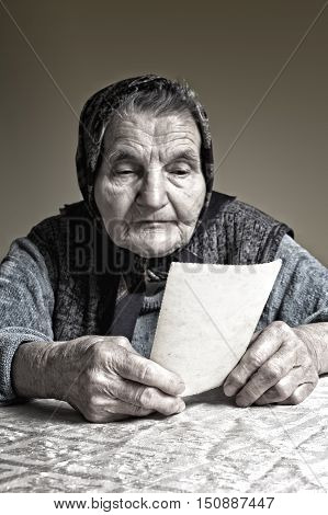 Elderly woman looking at old photos reminisce about the past. Selective focus on photos.