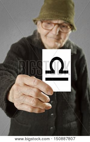 Elderly woman holding card with printed horoscope Libra sign. Selective focus on card and fingers.