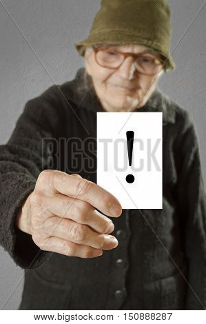 Elderly woman holding card with printed exclamation mark. Selective focus on card and fingers.