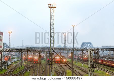 Old locomotives stand on railroad tracks of technical railway station - operational locomotive depot on autumn morning in fog. Transport infrastructure of Russia