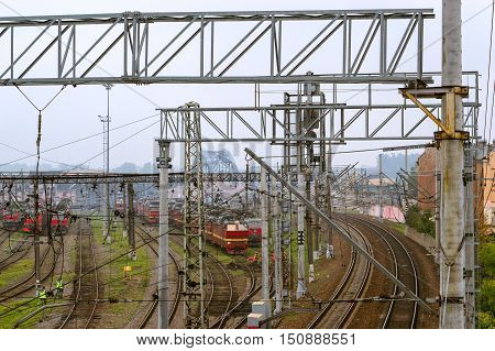 Old locomotives stand on railroad tracks of technical railway locomotive depot on autumn morning in fog. Workers in overalls serve rail journey. Transport infrastructure of Railways St. Petersburg