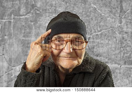 Elderly woman has an idea pointing with finger on her head.