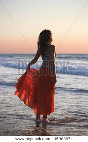 Woman holding the skirt at the sunset