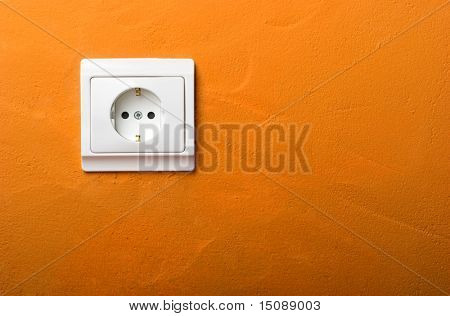 Electric wall plug at a orange wall