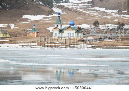 St. Nicholas Church In The Village Of Big Goloustnoye. View From Iced Baikal Lake