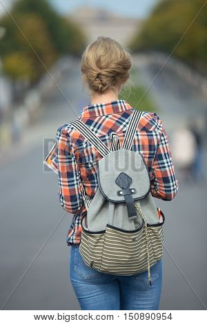 Young student girl walking down the city street with a backpack, in the middle of the roadway. Back to school concept photo, back view, vertical