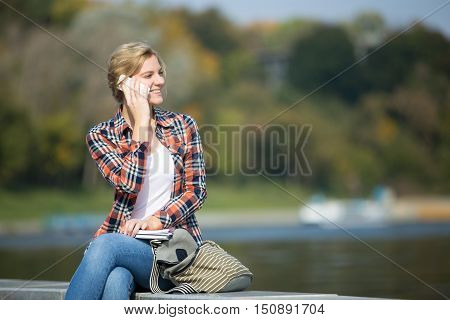 Portrait of a young attrractive girl sitting her legs crossed, head turned, at the bridge, talking on her phone, waterline behind, lifestyle, copyspace
