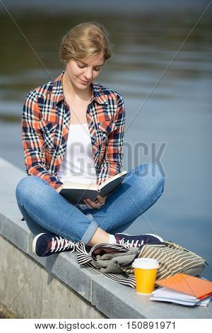 Portrait of a smiling girl sitting turkish at the bridge reading, coffee, copybook near, waterline behind. Back to school concept photo , lifestyle