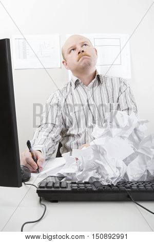 Thoughtful businessman writing while looking up with rejected papers on keyboard in office