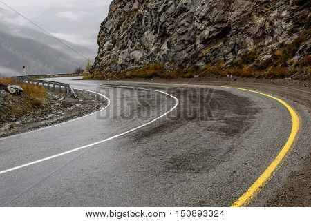 Scenic view of the hairpin bend wet winding road through the pass part of the mountain serpentine in autumn cloudy weather with fog