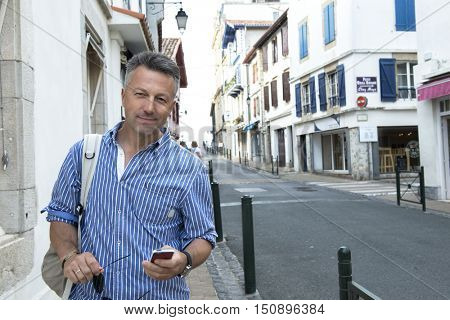 Male outdoor street portrait. Mid adult man walking city Saint Jean de Luz streets, France.