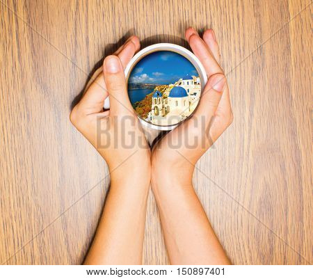 Woman holding cup with dream about vacation against wooden table. Top view. Conceptual photo