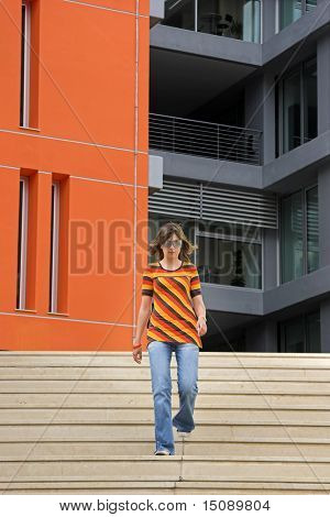 A young woman walking through the stairs of modern building