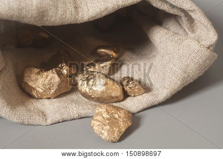 Gold nuggets spilling out from pouch on gray background