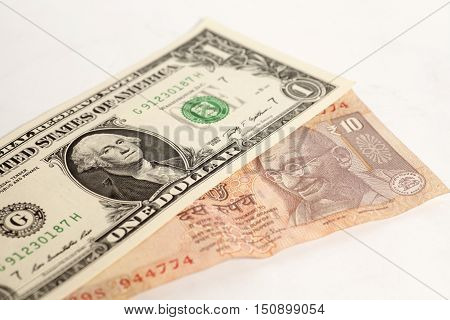 American one dollars and Indian ten rupee banknote on white background