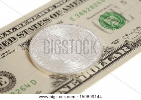 Silver bitcoin coin and one dollar banknote isolated on white