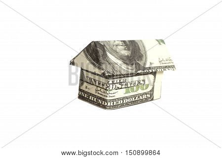 Origami house made of 100 dollar banknotes isolated on white background